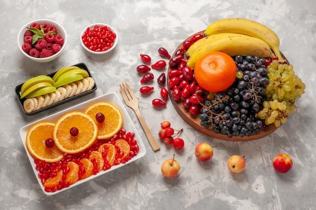 Draufsicht frische fruchtzusammensetzung hartriegel trauben bananen und orangen auf hellweißem oberflächenfruchtvitaminsaft mildes vitamin