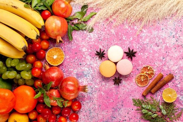 Draufsicht frische fruchtzusammensetzung mit französischen macarons auf hellrosa oberfläche