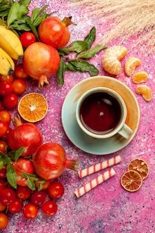 Draufsicht frische fruchtzusammensetzung mit tasse tee auf der hellrosa oberfläche