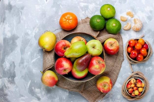 Draufsicht frische früchte äpfel mandarinen und mango auf hellweißem schreibtisch
