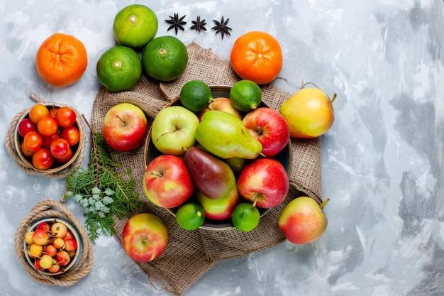 Draufsicht frische früchte äpfel mandarinen und mango auf hellweißer oberfläche