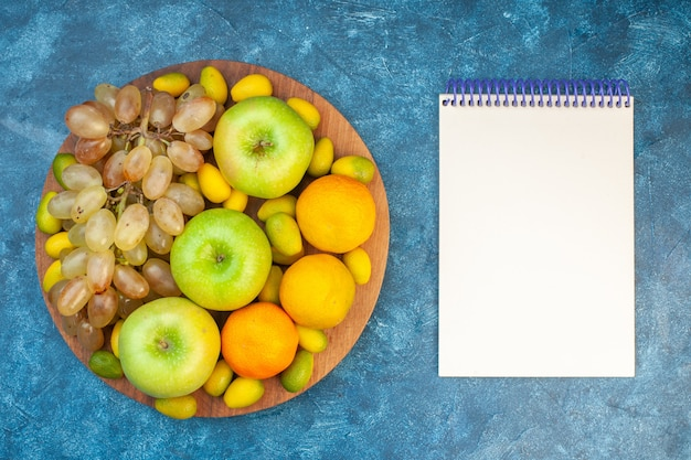 Draufsicht frische früchte äpfel mandarinen und trauben auf blauem tisch
