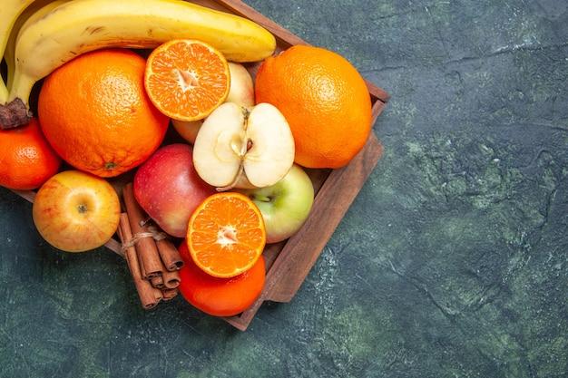 Draufsicht frische früchte bananen äpfel orangen zimtstangen auf holztablett auf dunklem hintergrund