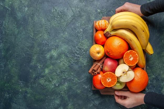 Draufsicht frische früchte orangen mandarinen äpfel bananen und zimtstangen auf holztablett in weiblichen händen auf dunklem hintergrund freiraum