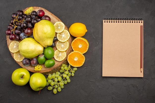 Draufsicht frische früchte trauben zitronenscheiben pflaumen und quitten auf dunkler oberfläche reife frische früchte gesundheit vitaminbaum