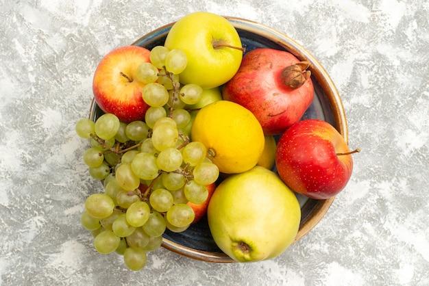 Draufsicht frische früchte zusammensetzung äpfel trauben und andere früchte auf weißer oberfläche frische milde früchte reife farbe