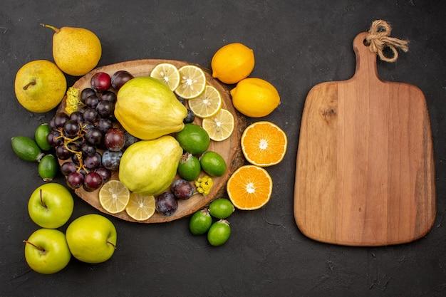 Draufsicht frische früchte zusammensetzung reife und reife früchte auf der dunklen oberfläche frucht reifes vitamin frisch