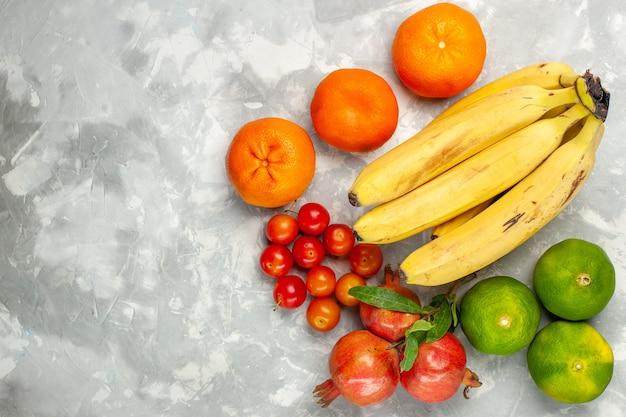Draufsicht frische gelbe bananen mit granatäpfeln und mandarinen auf hellweißem schreibtisch