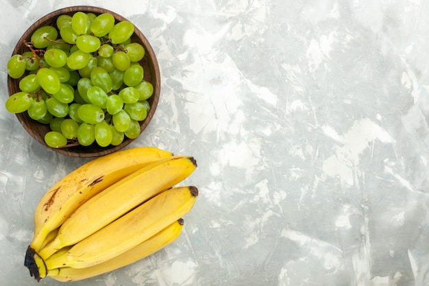 Draufsicht frische gelbe bananen weich und köstliche früchte mit trauben auf hellweißem schreibtisch