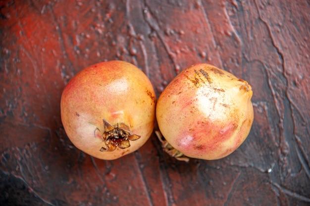 Draufsicht frische granatäpfel auf dunkelrotem holzhintergrund