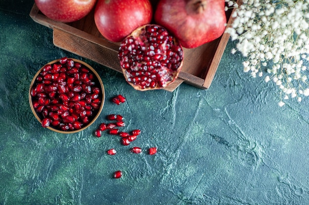 Draufsicht frische granatäpfel auf holzbrett kleine weiße blumen auf tischfreiraum