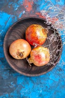 Draufsicht frische granatäpfel in holzschale auf blauem hintergrund