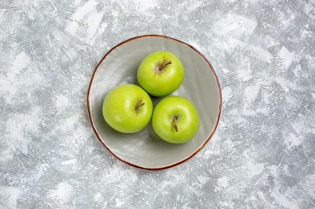 Draufsicht frische grüne äpfel innerhalb des tellers auf weißer oberfläche
