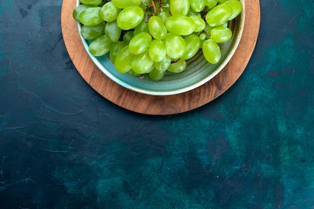 Draufsicht frische grüne trauben milde saftige früchte innerhalb platte auf dem dunkelblauen schreibtisch.
