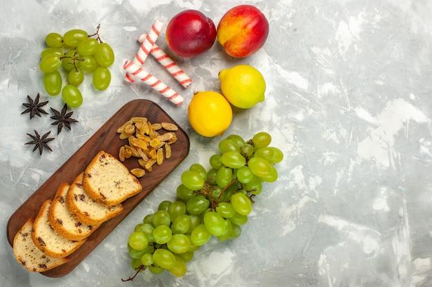 Draufsicht frische grüne trauben mit rosinen und kuchenscheiben auf hellweißem schreibtisch