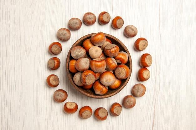 Draufsicht frische haselnüsse auf weißem schreibtisch nuss-snack-anlage walnuss erdnuss