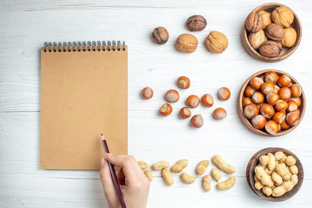 Draufsicht frische haselnüsse mit erdnüssen und walnüssen auf weißem tisch