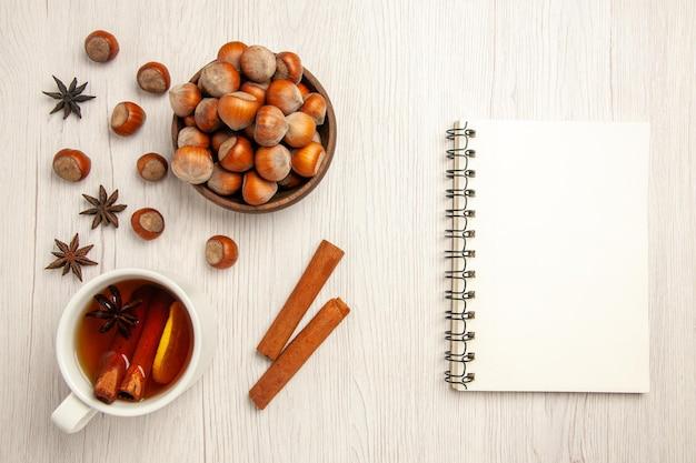 Draufsicht frische haselnüsse mit tasse tee auf weißem schreibtisch nuss-snack-getränk haselnuss walnuss