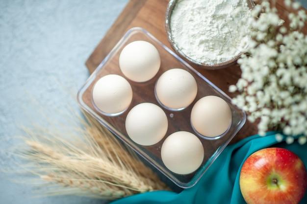 Draufsicht frische hühnereier auf leichtem tischtee-nachtischkuchen-zuckerfruchtkekskeks-süßem kuchenteig