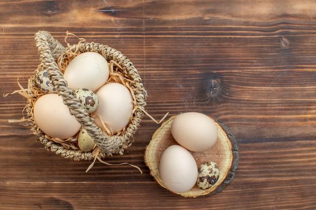 Draufsicht frische hühnereier mit wachteleiern auf braunem holzschreibtisch mahlzeit kuchen ofen kuchen backen kekse kochen