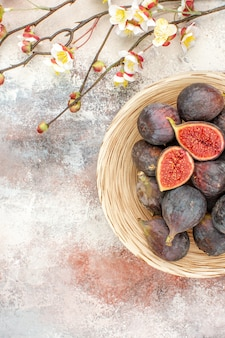Draufsicht frische kaki in weidenkorb-aprikosenblütenzweigen auf nacktem hintergrund