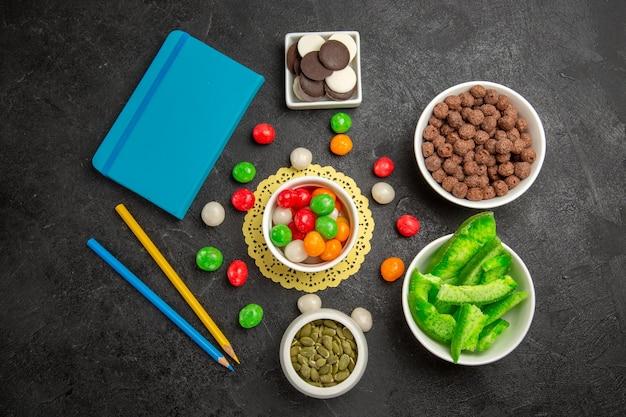 Draufsicht frische kürbiskerne mit keksen und bunten bonbons auf dunkelgrauem hintergrund regenbogenfarbensamensüßigkeiten