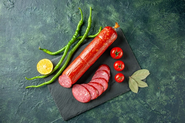 Draufsicht frische leckere wurst mit roten tomaten auf blauem hintergrund brot fleisch essen burger sandwich brötchen farbsalat