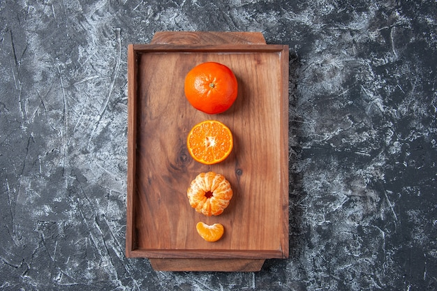 Draufsicht frische mandarinen geschälte mandarinen auf holztablett auf grauem hintergrund