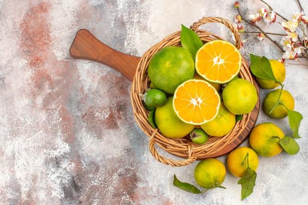 Draufsicht frische mandarinen im weidenkorb auf einem schneidebrett aprikosenblütenzweig auf nacktem hintergrund