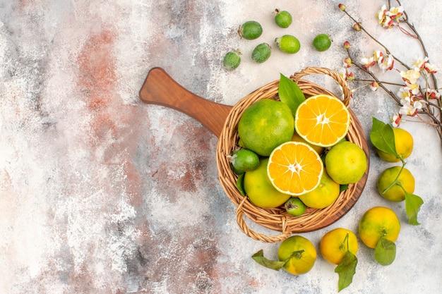 Draufsicht frische mandarinen im weidenkorb auf einem schneidebrett aprikosenblütenzweig feykhoas mandarinen auf nacktem hintergrund