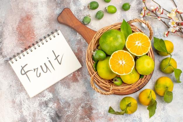 Draufsicht frische mandarinen im weidenkorb auf einem schneidebrett auf notebook auf nacktem hintergrund