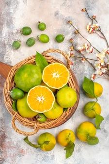 Draufsicht frische mandarinen im weidenkorb auf einem schneidebrett feykhoas aprikosenblütenzweig auf nacktem hintergrund