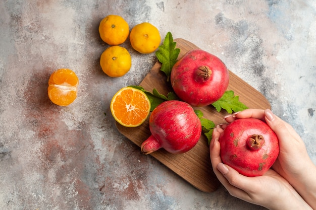 Draufsicht frische mandarinen mit roten granatäpfeln auf hellem hintergrund
