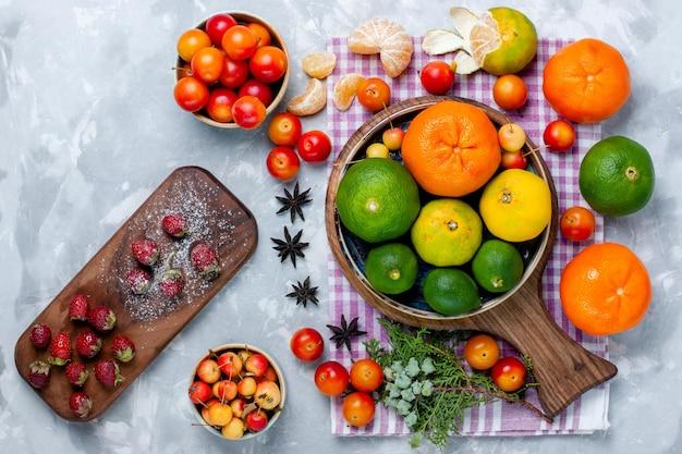 Draufsicht frische mandarinen mit zitronen und pflaumen auf hellweißem schreibtisch