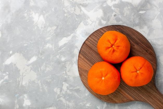 Draufsicht frische orange mandarinen ganze saure und milde zitrusfrüchte auf dem hellweißen hintergrund.
