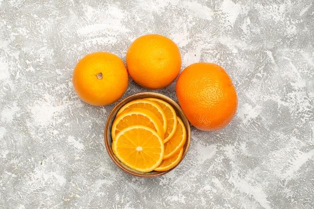 Draufsicht frische orangen geschnitten und ganze milde früchte auf dem weißen hintergrund zitrus exotischen tropischen fruchtsaft