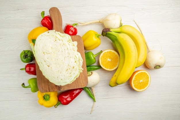Draufsicht frische paprika mit bananen und orange auf dem weißen hintergrund salat gesundes leben foto reife farbdiät