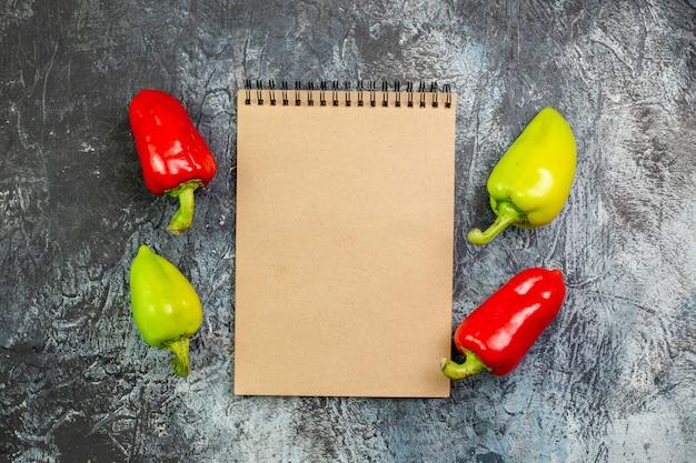 Draufsicht frische paprika mit notizblock auf dem hellgrauen tisch