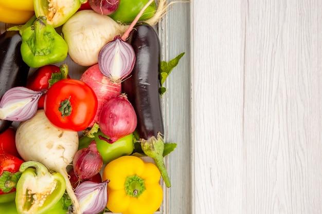 Draufsicht frische paprika mit rettich und zwiebeln auf weißem tisch