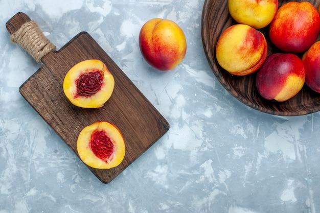 Draufsicht frische pfirsiche milde und leckere früchte in braunem teller auf dem hellweißen schreibtisch