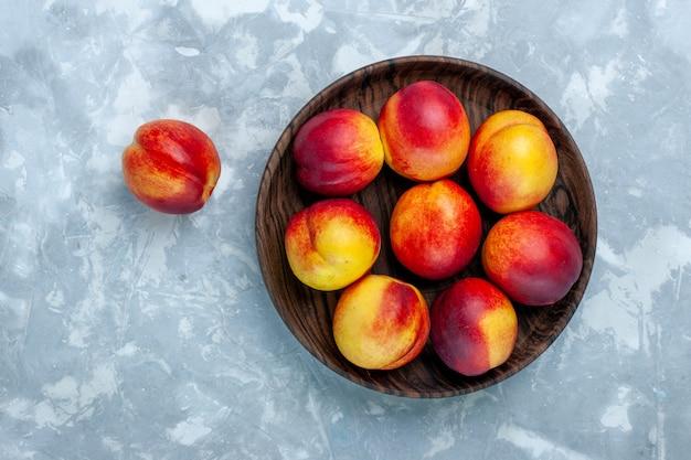 Draufsicht frische pfirsiche milde und leckere früchte in brauner platte auf der hellweißen oberfläche