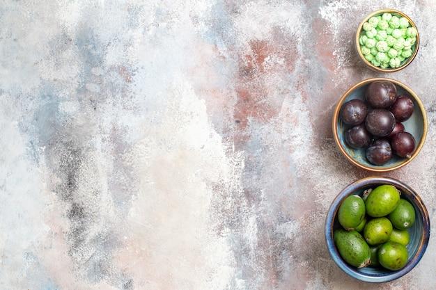 Draufsicht frische pflaumen mit feijoas und süßigkeiten