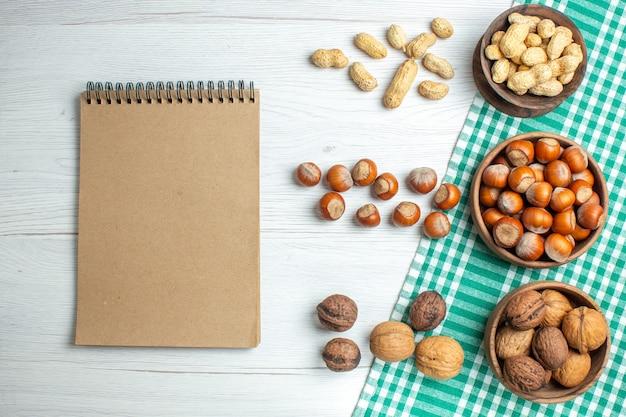 Draufsicht frische rohe haselnüsse mit erdnüssen auf weißem tisch