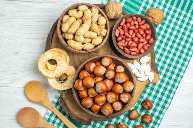 Draufsicht frische rohe haselnüsse mit erdnüssen auf weißen tafelnuss-pflanzennahrungs-snack-film-walnüssen