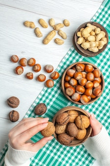 Draufsicht frische rohe haselnüsse mit erdnüssen und walnüssen auf weißem tisch