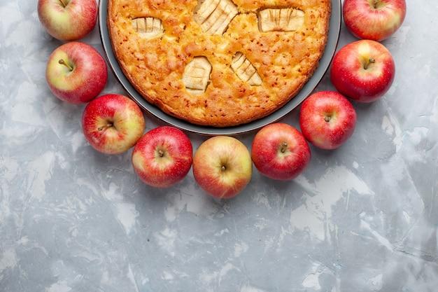 Draufsicht frische rote äpfel bilden kreis mit apfelkuchen auf dem hellen schreibtischfrucht frisches weiches reifes vitamin