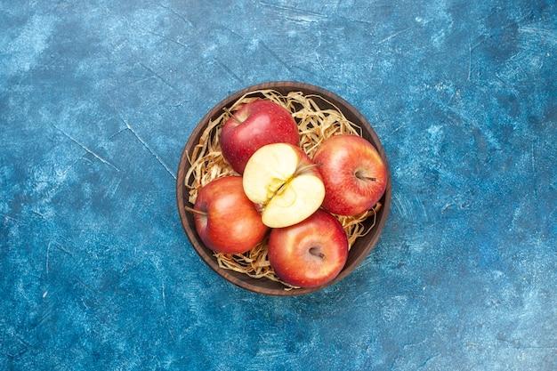 Draufsicht frische rote äpfel im teller auf blauem tisch