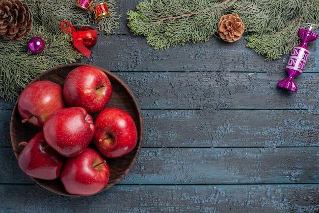 Draufsicht frische rote äpfel milde reife früchte auf der dunkelblauen schreibtischpflanze viele früchte vitaminbaum rote frische farbe