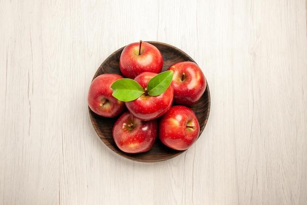 Draufsicht frische rote äpfel reife und ausgereifte früchte auf weißer schreibtischfrucht rote farbe baum frische pflanze