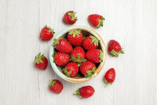 Draufsicht frische rote erdbeeren auf weißem schreibtisch